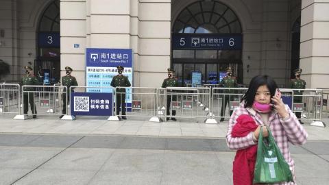 A woman talks on her cellphone as Chinese paramilitary police stand guard at an entrance to the closed Hankou Railway Station in Wuhan in central China's Hubei Province, Thursday, Jan. 23, 2020.