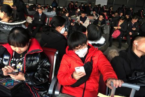 Pasajeros con mascarillas esperan un tren hacia Wuhan