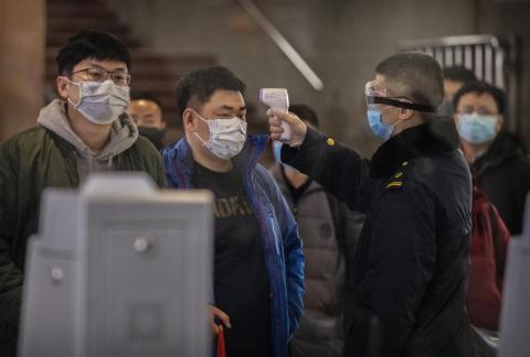 Pasajeros recién llegados en tren desde Wuhan son examinados en Pekín para detectar la presencia del coronavirus.