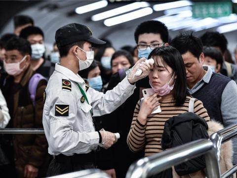 Gente con máscaras en Guangzhou, China.