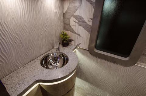 Quartz countertops adorn the bathroom in the rear of the portable home.
