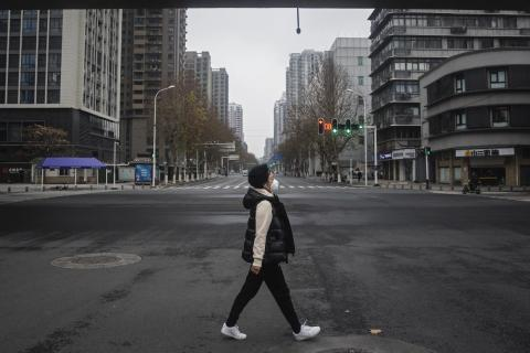 A woman walks on an empty road on January 27, 2020 in Wuhan, China. As the death toll from the coronavirus reaches 80 in China with over 2700 confirmed cases, the city remains on lockdown for a fourth day.