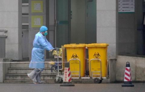 A staff member moves bio-waste containers past the entrance of the Wuhan Medical Treatment Center in Wuhan, China, where some people infected with a coronavirus were being treated on January 22, 2020.