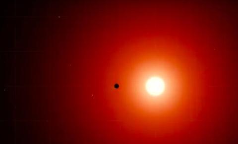 Fotografía de la estrella enana roja TOI 700 con uno de sus planetas pasado por delante.