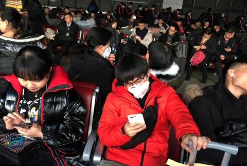 Passengers wear masks in the waiting area for a train to Wuhan at the Beijing West Railway Station on January 20, 2020.