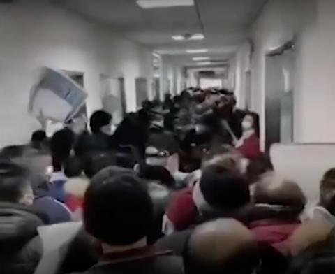 Una foto de un video del New York Times muestra a gente amontonándose en un pasillo de un hospital en Wuhan, China, en medio del brote de coronavirus.