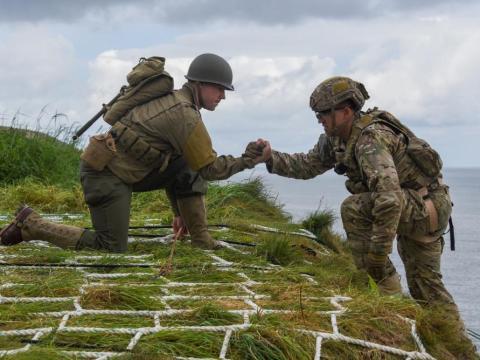Un soldado estadounidense vestido con un uniforme de la Segunda Guerra Mundial ayudando a otro con uniforme moderno del ejército.