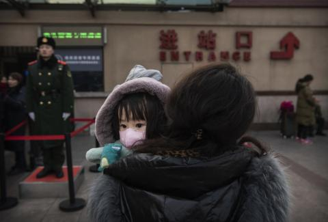 A girl wearing a face mask at Beijing's central railway station.