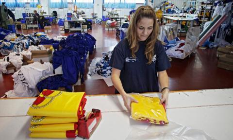 Una trabajadora empaqueta banderas en una fábrica