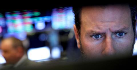 Trader mira con atención su terminal en Wall Street