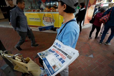Un vendedor reparte copias de un periódico con titulares sobre el brote de coronavirus en Hong Kong el 11 de enero de 2020.