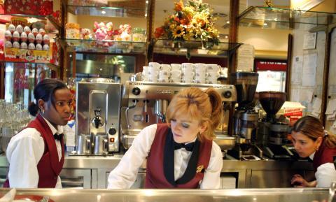 3 camareras trabajan tras la barra de una cafetería en Madrid