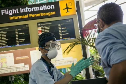 Information officer wearing protective mask, gloves and goggle, as prevention of novel coronavirus epidemic, gives directions to a passenger at international arrival gate of Bali Ngurah Rai International Airport in Kuta, Bali, Indonesia on February 4 2020
