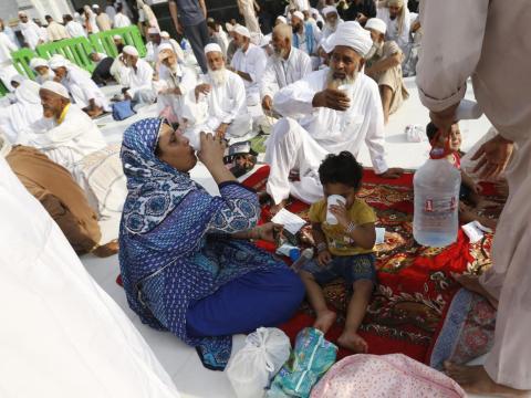 Gente sentada en la acera alrededor de la Gran Mezquita.