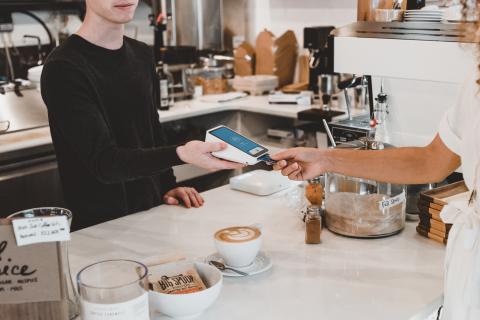 Una mujer pagando en una cafetería.