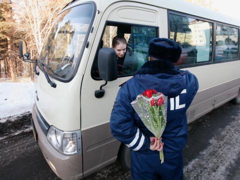Un policía de tránsito esconde un ramo de flores a sus espaldas cerca de Krasnoyarsk, Siberia.
