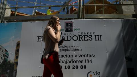 Una chica pasea junto a un anuncio inmobiliario.