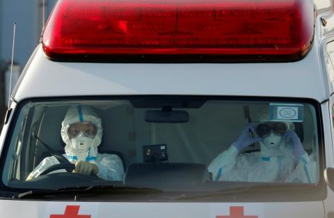 Conductores de una ambulancia llevan trajes protectores para transferir a los viajeros del Diamond Princess que han dado positivo del coronavirus.