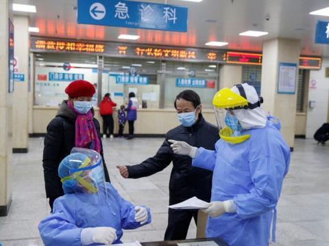 Las enfermeras con equipo de protección hablan con las personas en el área de recepción del First People's Hospital en Yueyang, provincia de Hunan, China, 28 de enero de 2020.