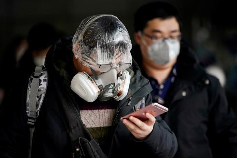 Hombre lleva una máscara mira el móvil.