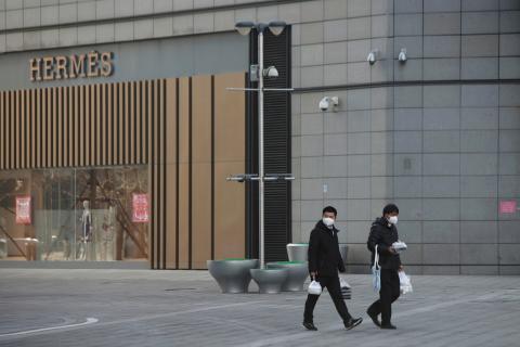 Dos ciudadanos de origen chino caminan con mascarillas delante de la tienda de la marca de lujo de Hermés