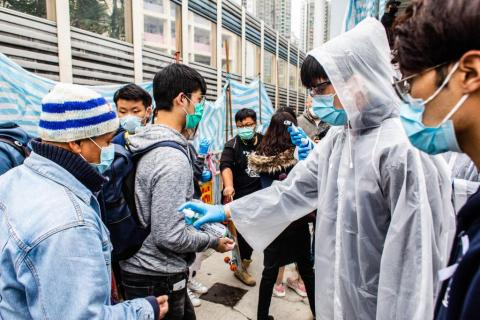 A volunteer offers hand sanitizer to passengers. In light of a coronavirus outbreak in China, Hong Kong district councilors and residents formed makeshift quarantine stations, screening passengers arriving from China. Citizens measured passenger's