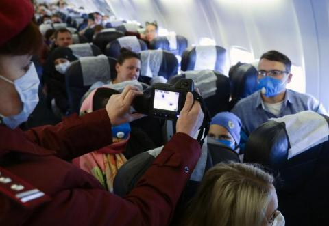 A Rospotrebnadzor (Russian Federal Service for Consumer Protection and Welfare Supervision) official uses thermal imaging devices to remotely measure temperature of passengers arriving at Novosibirsk International Airport from Sanya, China,