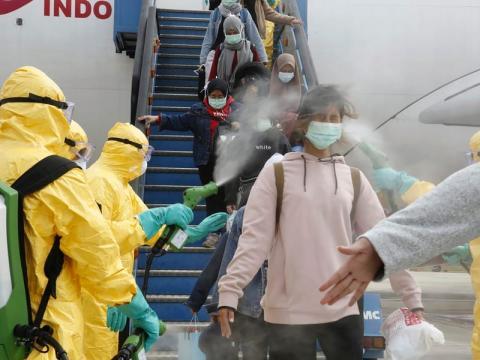 Los indonesios que llegaron desde Wuhan, China, fueron rociados con antiséptico en el aeropuerto Hang Nadim en la ciudad de Batam.