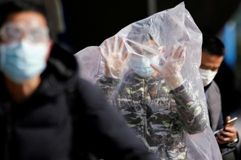 Un hombre camina encerrado en una bolsa de plástico en medio del brote del coronavirus de Wuhan