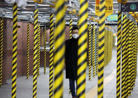 Un hombre camina por el metro de Seúl con una mascarilla para protegerse del brote de coronavirus