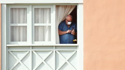 Un hombre con mascarilla se asoma en el hotel de Canarias bloqueado por el coronavirus.