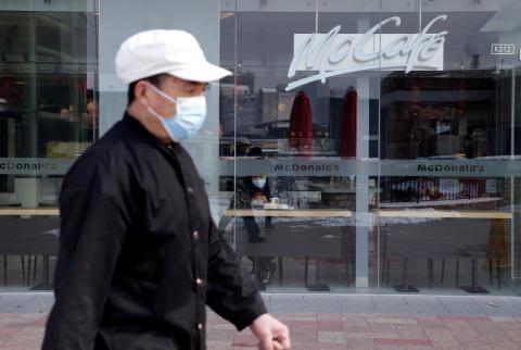 Un hombre con una mascarilla pasa por delante de un establecimiento de Mcdonald's en Pekín