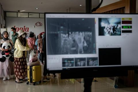 Passengers from an international flight have their temperature checked as they pass a thermal scanner monitor upon arrival at the Adisucipto International Airport on January 23, 2020 in Yogyakarta, Indonesia.