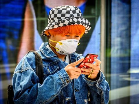 Mujer con máscara revisa su teléfono fuera de un centro comercial en Bangkok el 4 de febrero.