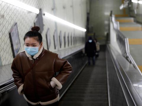 Mujer con una máscara facial en una estación de metro en Pekín.