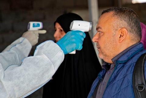 Un miembro del equipo médico le toma la temperatura en la frontera de Shalamjah entre Irán e Iraq el 21 de febrero de 2020.