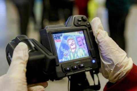 A sanitary and quarantine control official screens the temperatures of arriving passengers at Vnukovo International Airport; temperature screening using thermal imaging devices is under way at Vnukovo Airport