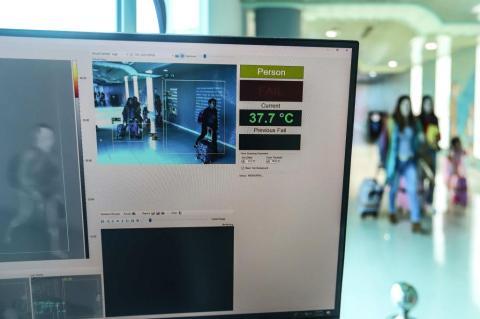 Passengers walk through a thermal scanner upon their arrival at Sultan Mahmud Badaruddin II International airport in Palembang, Indonesia on January 23, 2020.