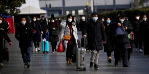 Los pasajeros con máscaras caminan en la estación de tren de Shanghai.