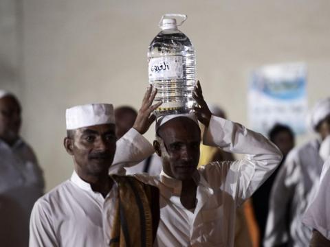 Un hombre llevando una garrafa de agua.