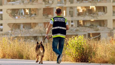 Un perro de la Unidad Canina pasea con un agente de la Policía Nacional.