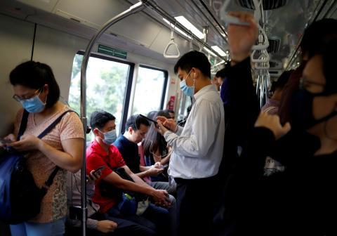 Personas en un autobús de Singapur ante el miedo del coronavirus.