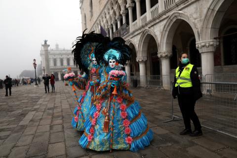 Personas disfrazadas pasean por la plaza de San Marcos en Venecia en medio del brote del coronavirus, que ha cancelado los actos oficiales del carnaval.