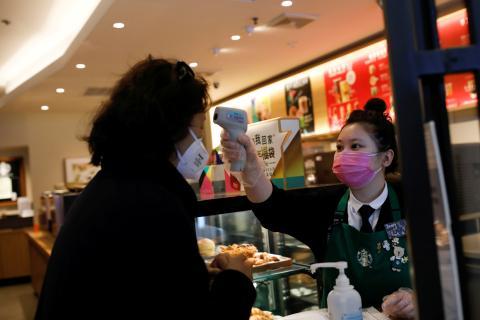 Una trabajadora de un Starbucks en Pekín utiliza un termómetro para medir la temperatura de un cliente en medio del brote del coronavirus.