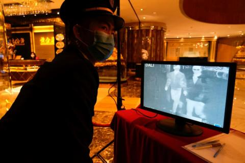 A security guard monitors thermal scanners that detect temperatures of visitors at the closed Grand Lisboa casino and hotel.
