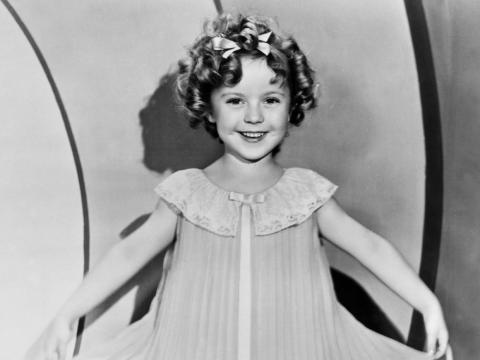 Shirley Temple as a child star wearing an accordion pleated dress.