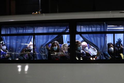 US passengers leaving the Daikoku Pier Cruise Terminal in Yokohama port, next to the Diamond Princess cruise ship, on February 17.