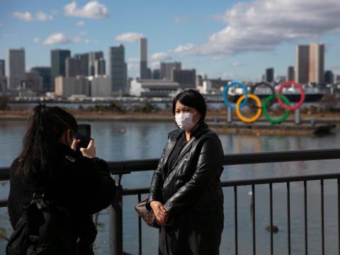 Una turista con máscara se hace una foto frente a los anillos olímpicos en el distrito de Odaiba de Tokio.