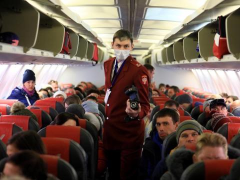 Auxiliar de vuelo llevando una máscara.