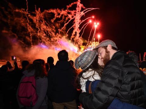 Una pareja se besa mientras asiste a un espectáculo de fuegos artificiales.